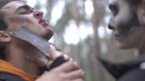 Halloween. Scary woman with a terrible make-up threatens the guy with a knife. Scary woman with a terrible make-up threatens the guy with a knife. Halloween stock footage