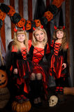 Halloween scene with three attractive witches. Young mother and two little daughters twins, in costumes in black and red indoors Stock Image
