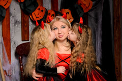 Halloween scene with three attractive witches. Young mother and two little daughters twins, in costumes in black and red indoors, sisters kissing their mommy Royalty Free Stock Photography