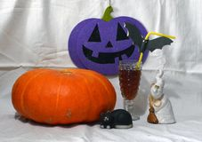 Halloween scenery with a ghost, a black cat, a pumpkin and a glass stock photography