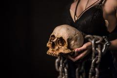 Halloween-Schädel auf der Hand eines Mädchens mit einer Kettensäge Lizenzfreies Stockfoto