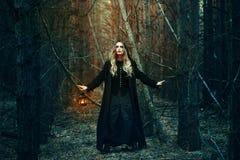 Halloween schönes Mädchen mit einer Laterne in einem schwarzen Kleid im Wald Stockfotografie