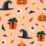 Halloween seamless pattern with pumpkins, hats, bats, candy corns and gifts. Vector illustration Stock Photos