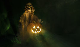 Halloween setup. A ghostly ghoul guarding a smiling Halloween pumpkin Royalty Free Stock Photos