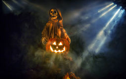 Halloween setup. A ghostly ghoul surrounded by fog is guarding a smiling Halloween pumpkin Stock Photo