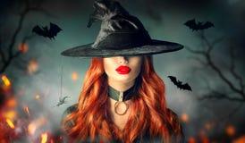 halloween sexig häxa för stående Härlig kvinna i häxahatt med långt lockigt rött hår royaltyfria bilder