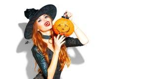 halloween Sexig häxa med ljus feriemakeup Härlig ung kvinna som poserar i häxadräkt med pumpalyktan arkivbilder