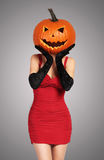 Halloween. Sexy lady in red with big pumpkin on head. Royalty Free Stock Photos