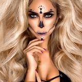Halloween Sexy naked Witch portrait. Beautiful young woman in witches makeup with long curly colorful hair and sexy lingerie. Wide