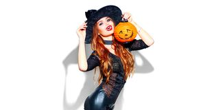 Halloween. witch with bright holiday makeup. Beautiful young woman posing in witches costume with pumpkin lantern royalty free stock photography