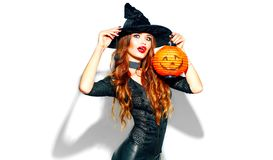 Halloween. witch with bright holiday makeup. Beautiful young woman posing in witches costume with pumpkin lantern. Over white background stock photos