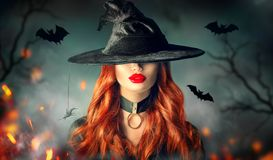 Halloween. witch portrait. Beautiful woman in witches hat with long curly red hair royalty free stock images