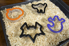 Halloween Shaped Puffed Rice Cereal Treats. Puffed rice cereal treats in a tray with halloween shaped cookie cutters; pumpkin, cat, bat and ghost royalty free stock image