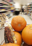 Halloween shopping in a supermarket. Pumpkins and indian corn in the trolley. Motion blur and focus on the pumpkins Stock Image