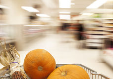 Halloween shopping in a supermarket, landscape. Halloween shopping in a supermarket: pumpkins and indian corn in the trolley, Motion blur and focus on the Stock Images
