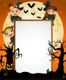 Halloween sign with little boy witch and little girl witch and cat costume and spooky tree Stock Photo