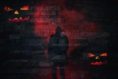 Halloween-silhouet van een enge persoon in rode rook met kwade pompoengezichten op een bakstenen muurachtergrond royalty-vrije illustratie