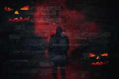 Halloween silhouette of a scary person in red smoke with evil pumpkin faces on a brick wall background royalty free stock photography