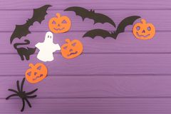 Halloween silhouettes cut out of paper made of corner frame. With pumpkins, bats, cat, spider, and ghost on purple board. Halloween holiday. Copy space Royalty Free Stock Photos