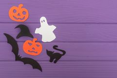 Halloween silhouettes cut out of paper made of corner frame. With pumpkins, bat, cat, ghost, hat on purple board. Halloween holiday. Copy space Stock Photography