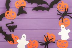 Halloween silhouettes cut out of paper made of round frame. With pumpkins, bats, cat, spider, hat and ghosts on purple board. Halloween holiday. Copy space Royalty Free Stock Image