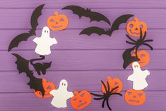 Halloween silhouettes cut out of paper made of round frame. With pumpkins, bats, cat, spider, hat and ghosts on purple board. Halloween holiday. Copy space Stock Photo