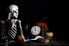 Halloween Skeleton. A skeleton checking the time and reaching for old iron keys, clock is about to strike midnight and he is on his way to haunt for Halloween Royalty Free Stock Image