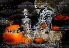 Halloween Skeletons Party. Three Halloween skeletons laughing while sitting together on straw bales drinking bottled beer while large spiders crawl about and