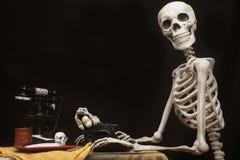 Halloween-Skelett an einem Tisch mit Schreibmaschine, Telefon und Plätzchen Stockbild