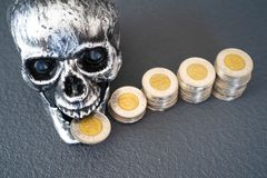 Halloween Skull With Stacks of Coins on display stock photo