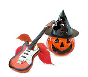 Halloween song with guitar and pumpkin. Celebrating Halloween with guitar and scary pumpkin decoration. Isolated on white background Royalty Free Stock Image