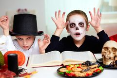 Halloween sorcery. Photo of twin eerie boys looking at camera with frightening look Stock Photos