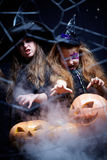 Halloween sorcery. Two girls dressed in witches making the pumpkins smoke behind the cobweb Stock Photo