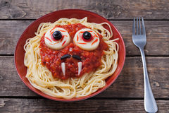 Halloween spaghetti face with big eyeballs fangs. And moustaches in noodle dish with red tomato sauce, for halloween celebration party on vintage table Royalty Free Stock Photography