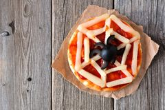 Halloween spider web mini pizza over rustic wood. Halloween spider web mini pizza over a rustic wooden background Royalty Free Stock Photo