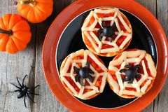 Halloween spider web mini pizzas on black and orange plate. Over a rustic wood background Stock Images