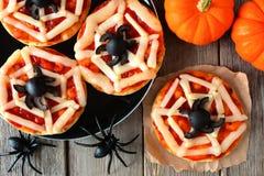 Halloween spider web mini pizzas overhead scene on rustic wood Royalty Free Stock Photos