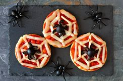 Halloween spider web mini pizzas, overhead view on slate. Halloween spider web mini pizzas, overhead view on a slate server with spiders Royalty Free Stock Images