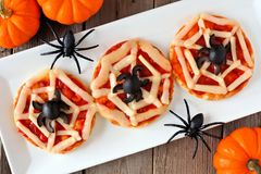 Halloween spider web mini pizzas, table scene on white plate. Halloween spider web mini pizzas on white plate over a rustic wooden background Royalty Free Stock Image