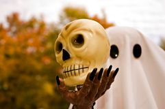 Halloween Spook and Skull. Halloween figure of a ghost holding a skull Royalty Free Stock Images