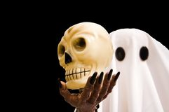 Halloween Spook and Skull - Isolated. Halloween figure of a ghost holding a skull, isolated on a black background Royalty Free Stock Photo
