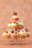 Halloween Spooky Cakes. Pumpkin cupcakes for Halloween on cakestand with various toppings Stock Photography
