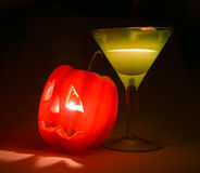 Halloween still-life. Red pepper and yellow glass on a black background Stock Image