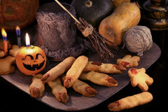 Halloween still life with finger cookies and witch objects in candle light. Halloween background with finger cookies and witch magic objects in candle light Stock Photo