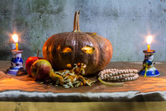 Halloween still life with pumpkins, apple, candles and rosary Royalty Free Stock Photo