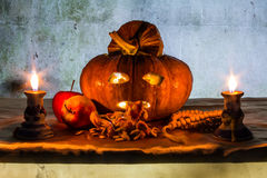 Halloween still life with pumpkins, apple, candles and rosary Royalty Free Stock Photos