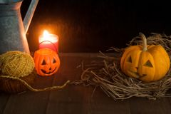 Halloween still life with pumpkins and candle on wooden floor and dark background Stock Photos