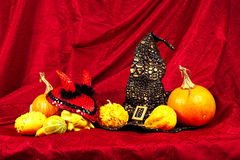Halloween still life with pumpkins, witch hat and a devil red hat Stock Photo