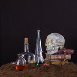 Halloween still life with skull, books, candles and bottles of p Stock Image