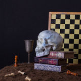 Halloween still life with skull, books and goblet of wine stock images